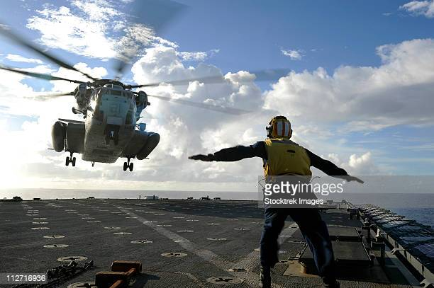 Aviation Boatswain's Mate directs a CH-53E Super Stallion onto the flight deck of USS Harpers Ferry.