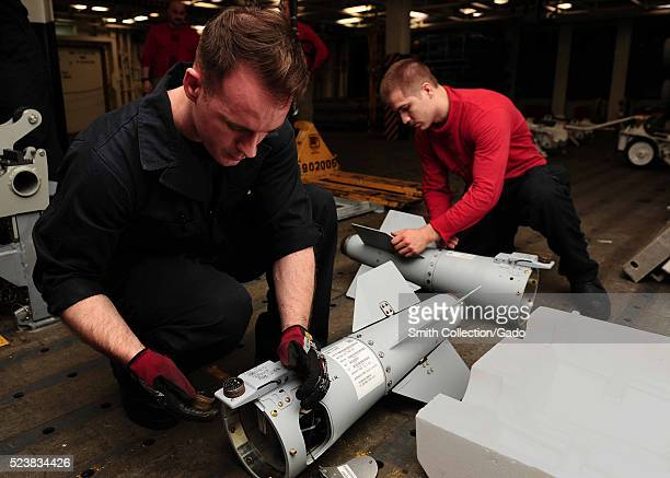 Aviation Ordnanceman Airmen Robert Perine and Nicholas Mommers inspect ordnance aboard the aircraft carrier USS Theodore Roosevelt CVN 71 Arabian...