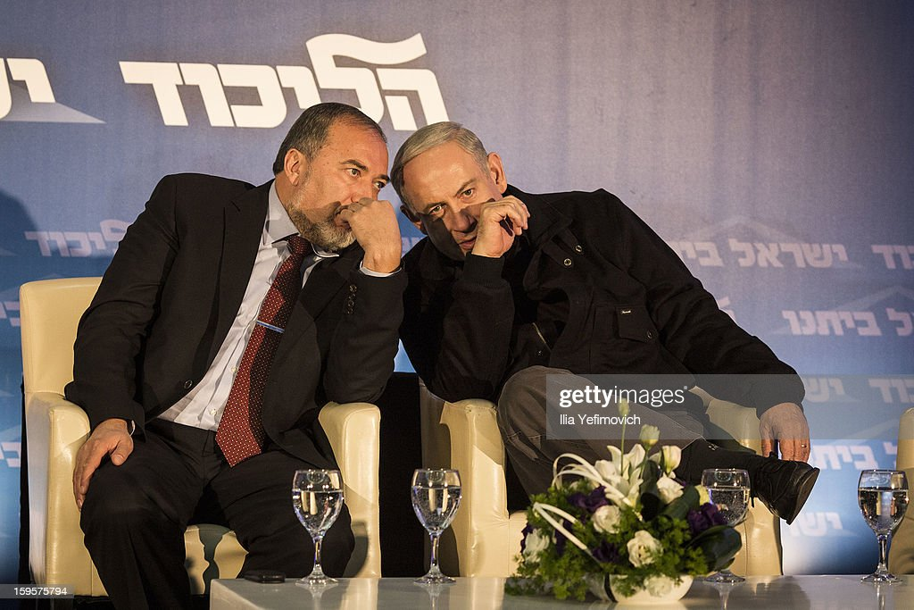 Avigdor Lieberman (L) and Israeli Prime Minister Benjamin Netanyahu wait to speak at a rally ahead of the national elections on January 16, 2013 in Ashdod, Israel.General elections will be held on January 22, 2013 to decide members of parliament and whether Benjamin Netanyahu will receive another term in office at Prime Minister.