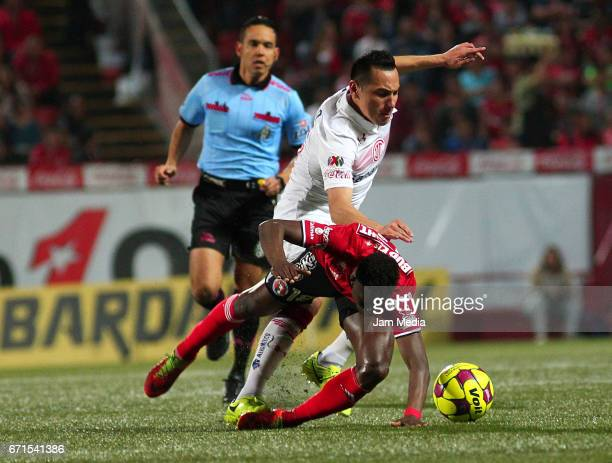 Aviles Hurtado of Tijuana falls to the ground as Antonio Rios steals the ball during 15th round match between Tijuana and Toluca as part of the...