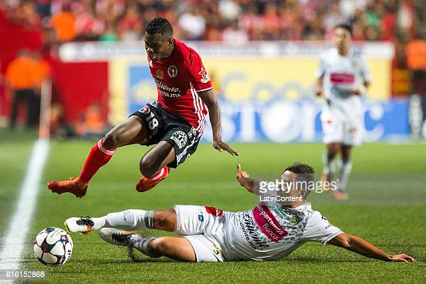 Aviles Hurtado of Tijuana jusmp to avoid the slide by William Paredes of Chiapas during the 14th round match between Tijuana and Chiapas as part of...
