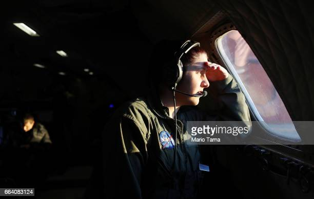 NASA avionics technician Lauren Prinski looks out a window of NASA's Operation IceBridge research aircraft before takeoff from Thule Air Base on...