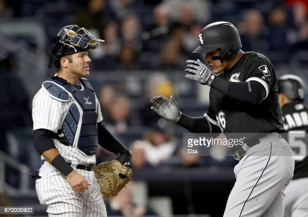 Avisail Garcia of the Chicago White Sox celebrates his three run home run as he crosses the plate with Austin Romine of the New York Yankees looking...