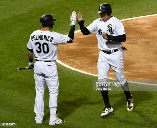 Avisail Garcia of the Chicago White Sox is greeted by Nicky Delmonico after scoring against the Los Angeles Angels of Anaheim during the third inning...