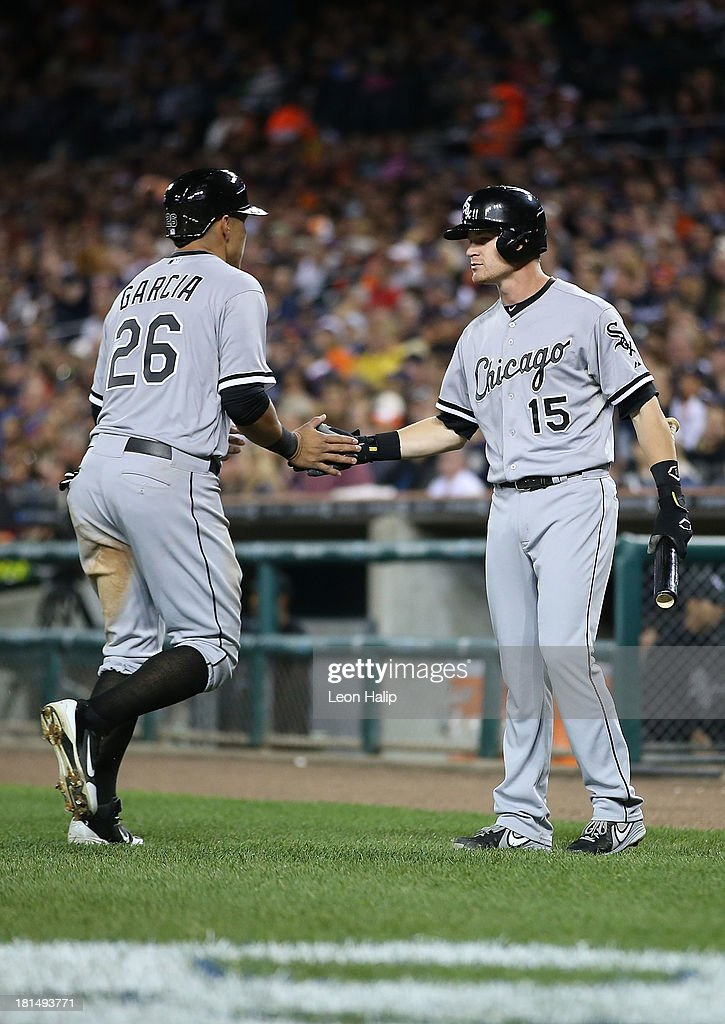 Avisail Garcia #26 of the Chicago White Sox scores on the single by Jeff Keppinger #7 and is congratulated by Gordon Beckman #15 in the seventh inning of the game against the Detroit Tigers at Comerica Park on September 21, 2013 in Detroit, Michigan.