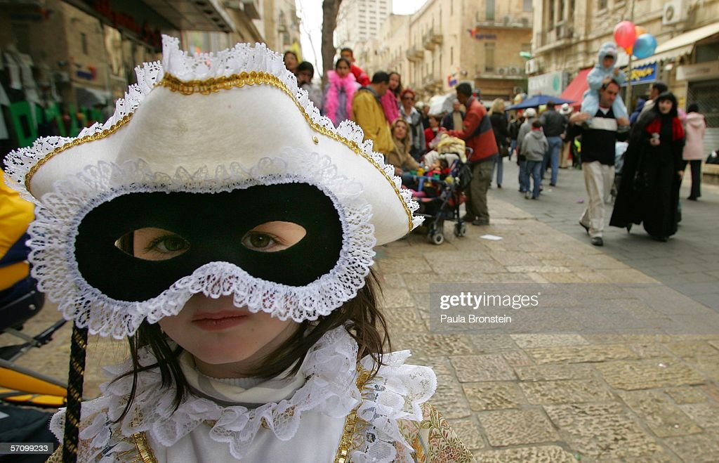 Avital Politi dressed as a princess from Venice looks out from her mask during the Jewish festival of Purim March 152006 in Jerusalem Israel Acting...