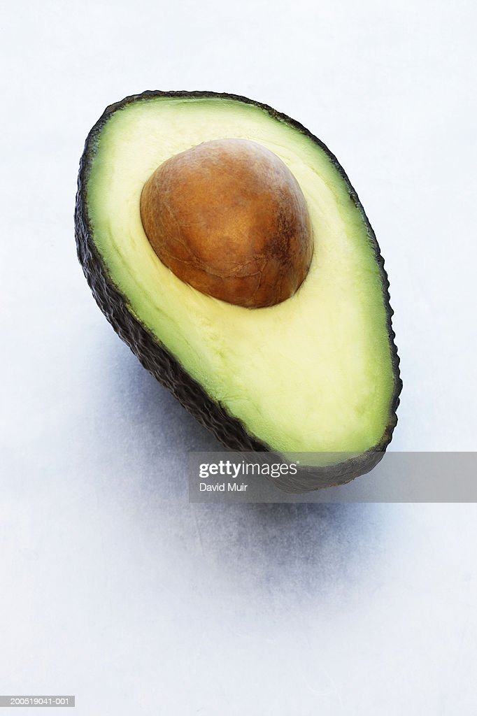 Avocado cut in half, with stone, close-up : Stock Photo