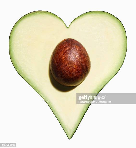 Avocado cut into the shape of a heart on a white background