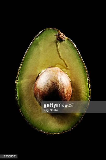 Avocado cut is illuminated black background