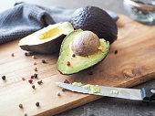 Aufgeschnittenes Avocado und Pfefferkörner auf einem Holzbrett und daneben ein Messer.