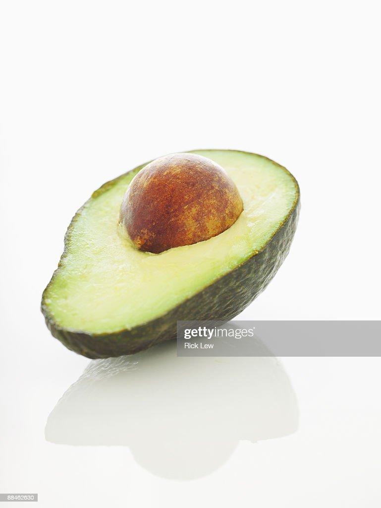 avocado half with pit : Stock Photo
