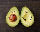 An avocado parent and child in embrace beside another avocado who is sad that is it without a child or baby