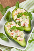 Avocado stuffed with crab, cucumber, egg, red onion and sauce mayonnaise on white plate