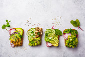 Avocado toasts with different toppings, top view, white background. Plant based diet concept.