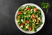 Avocado, tomato, chickpeas, spinach and cucumber salad. Top view