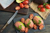 Presentación gastronómica de 3 piezas de medio aguacate cubierto con 2 lonchas de salmón ahumado, acompañado con tomate cherry sazonado con orégano, sal, pimienta y perejil.