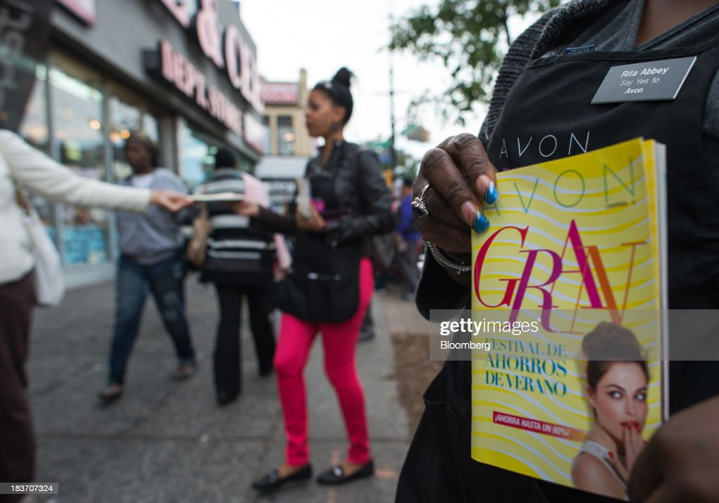 Avon Products Inc. representative Rita Abbey, right, holds a Spanish-language brochure during an Avon Magic Bus recruiting event in the Bronx borough of New York, U.S., on Tuesday, Oct. 8, 2013. Beauty and personal-care sales and earnings are expected to exceed those of household products in 2013 with recovering mass-beauty companies like Avon positioned at the top end of 2013 consensus earnings expectations. Photographer: Ron Antonelli/Bloomberg via Getty Images