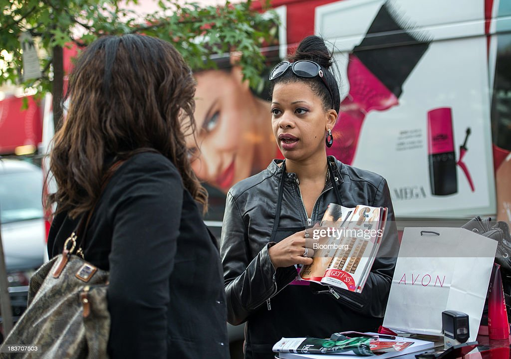Avon Products Inc. sales representative Haizel McIntyre, right, shows Glory Robinson beauty products inside a brochure during an Avon Magic Bus recruiting event in the Bronx borough of New York, U.S., on Tuesday, Oct. 8, 2013. Beauty and personal-care sales and earnings are expected to exceed those of household products in 2013 with recovering mass-beauty companies like Avon positioned at the top end of 2013 consensus earnings expectations. Photographer: Ron Antonelli/Bloomberg via Getty Images