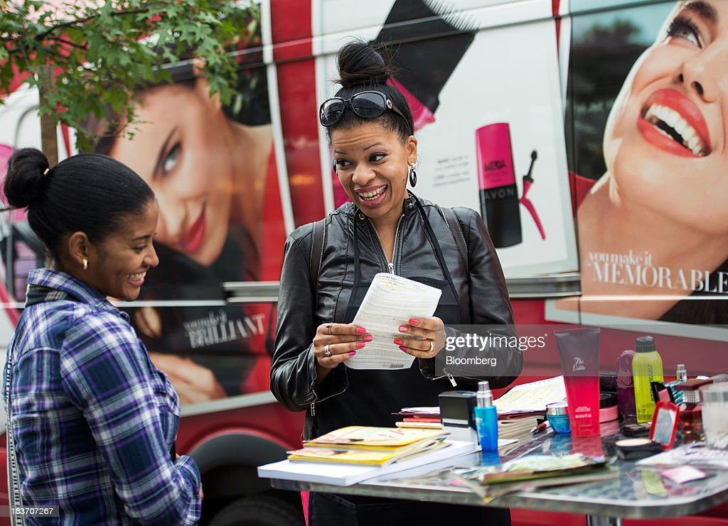 Avon Products Inc. sales representative Haizel McIntyre, right, speaks to Penelope Sanchez as she signs up to be a sales representative during an Avon Magic Bus recruiting event in the Bronx borough of New York, U.S., on Tuesday, Oct. 8, 2013. Beauty and personal-care sales and earnings are expected to exceed those of household products in 2013 with recovering mass-beauty companies like Avon positioned at the top end of 2013 consensus earnings expectations. Photographer: Ron Antonelli/Bloomberg via Getty Images ** Local Caption *** Haizel McIntyre; Penelope Sanchez