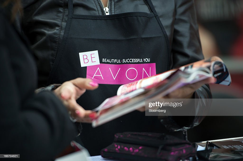 Avon Products Inc. sales representative Haizel McIntyre shows a woman a brochure of products during an Avon Magic Bus recruiting event in the Bronx borough of New York, U.S., on Tuesday, Oct. 8, 2013. Beauty and personal-care sales and earnings are expected to exceed those of household products in 2013 with recovering mass-beauty companies like Avon positioned at the top end of 2013 consensus earnings expectations. Photographer: Ron Antonelli/Bloomberg via Getty Images