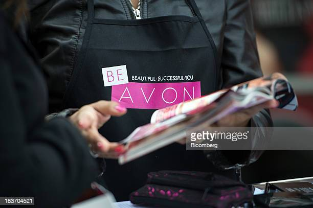 Avon Products Inc sales representative Haizel McIntyre shows a woman a brochure of products during an Avon Magic Bus recruiting event in the Bronx...