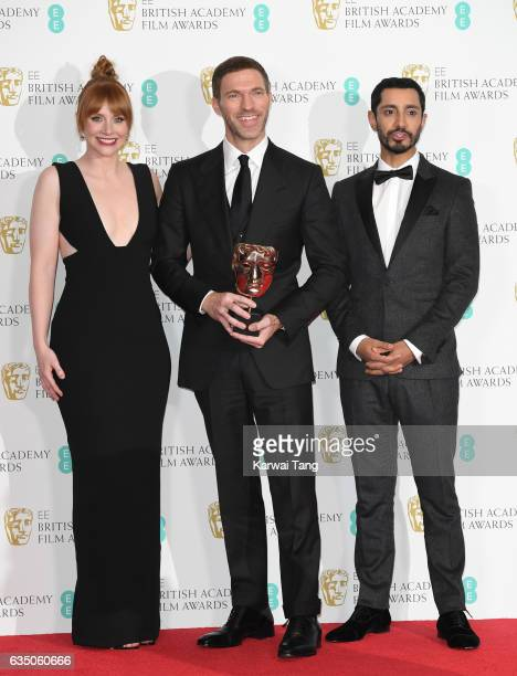 Award presenters Bryce Dallas Howard and Riz Ahmed pose with animated Film Award winner Travis Knight in the winners room at the 70th EE British...