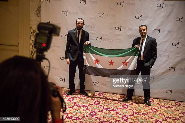 Awardees Abdelaziz Alhamza and Abu Mohamed members of Raqqa is Being Slaughtered Silently pose with a Syrian flag at the Committee to Protect...
