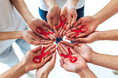 Group of young multiracial woman with red ribbons in hands are struggling against HIV/AIDS. AIDS awareness concept.