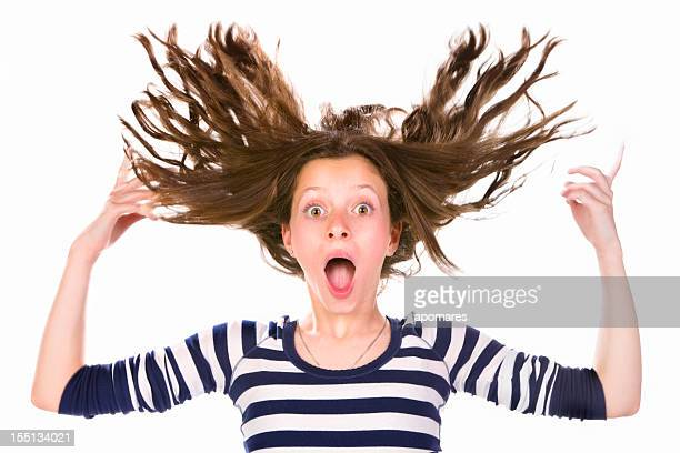 Awe teenage girl with flying hair and surprised expression