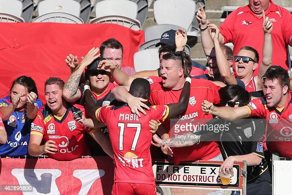 Awer Mabil of Adelaide celebrates with fans after scoring a goal during the round 16 ALeague match between the Central Coast Mariners and Adelaide...