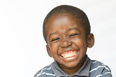 Huge Smile on a little African boy making a facial expression. Here he is laughing hard at the camera. Isolated on white.