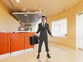 Awkward Hispanic businessman holding briefcase in office lobby