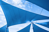 Awnings in sails shape over cloudy sky background. Blue toned photo