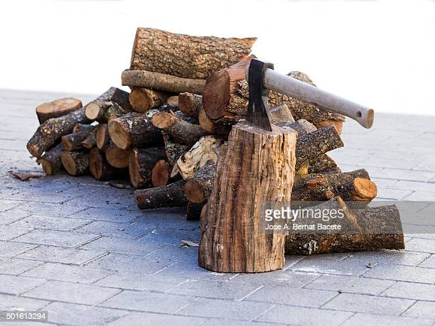 Axe fixed on a heap of trunks of wood of pine and oak