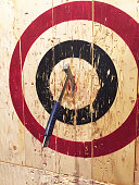 A large metal ax is embedded into a wooden target while playing the game of axe throwing.