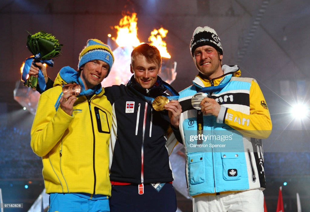 <a gi-track='captionPersonalityLinkClicked' href=/galleries/search?phrase=Axel+Teichmann&family=editorial&specificpeople=773876 ng-click='$event.stopPropagation()'>Axel Teichmann</a> of Germany receives the silver medal, <a gi-track='captionPersonalityLinkClicked' href=/galleries/search?phrase=Petter+Northug&family=editorial&specificpeople=800847 ng-click='$event.stopPropagation()'>Petter Northug</a> of Norway receives the gold medal and <a gi-track='captionPersonalityLinkClicked' href=/galleries/search?phrase=Johan+Olsson&family=editorial&specificpeople=724246 ng-click='$event.stopPropagation()'>Johan Olsson</a> of Sweden receives the bronze medal during the medal ceremony for the men's 50 km, mass start cross-country skiing held during the Closing Ceremony of the Vancouver 2010 Winter Olympics at BC Place on February 28, 2010 in Vancouver, Canada.