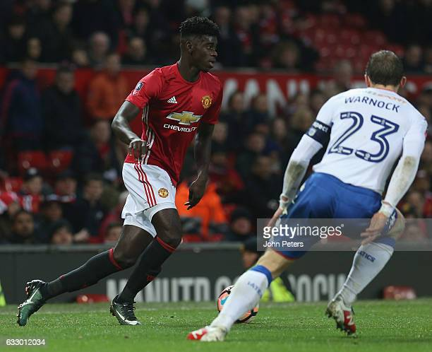 Axel Tuanzebe of Manchester United in action with Stephen Warnock of Wigan Athletic during the Emirates FA Cup Fourth Round match between Manchester...