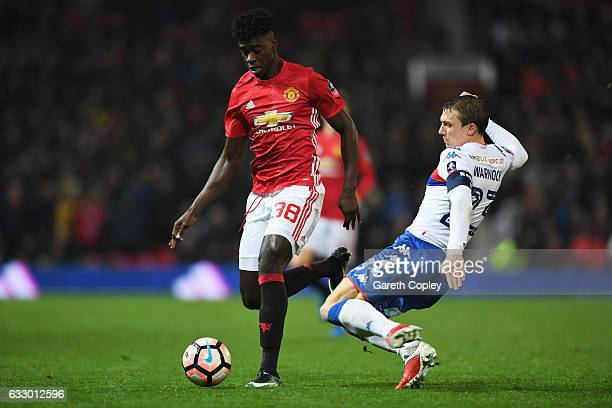 Axel Tuanzebe of Manchester United is tackled by Stephen Warnock of Wigan Athletic during the Emirates FA Cup Fourth round match between Manchester...