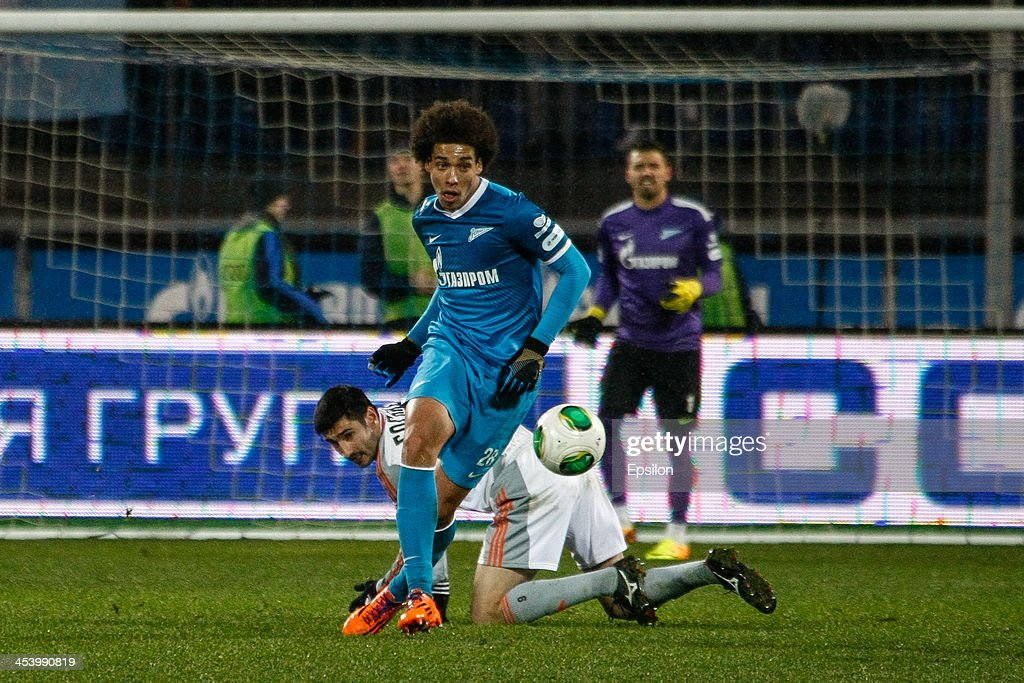 Axel Witsel of FC Zenit St. Petersburg (C) in action against Spartak Gogniyev of FC Ural Sverdlovsk Oblast during the Russian Football League Championship match between FC Zenit St. Petersburg and FC Ural Sverdlovsk Oblast at the Petrovsky stadium on December 6, 2013 in St. Petersburg, Russia.