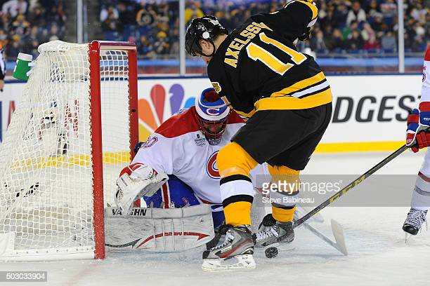 J Axelsson of the Boston Bruins against Jose Theodore of the Montreal Canadiens in the alumni game December 31 2015 during 2016 Bridgestone NHL...