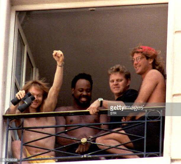 Axl Rose leader of the rock group Guns N' Roses greets supporters 04 Dec from his hotel window together with other musicians The group will perform...