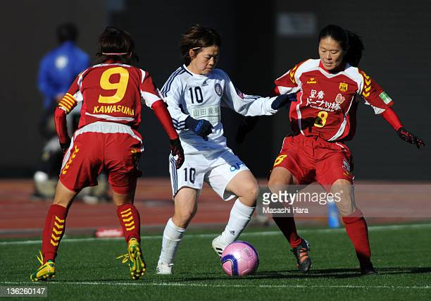 Aya Miyama of Okayama Yunogo Belle battles for the ball with Nahomi Kawasumi and Homare Sawa of INAC Kobe Leonessa during the All Japan Women's...