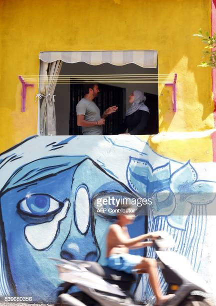 Ayad Nasser the property developer behind the 'Ouzville' project speaks with a woman inside her repainted house in Beirut's southern Ouzai...