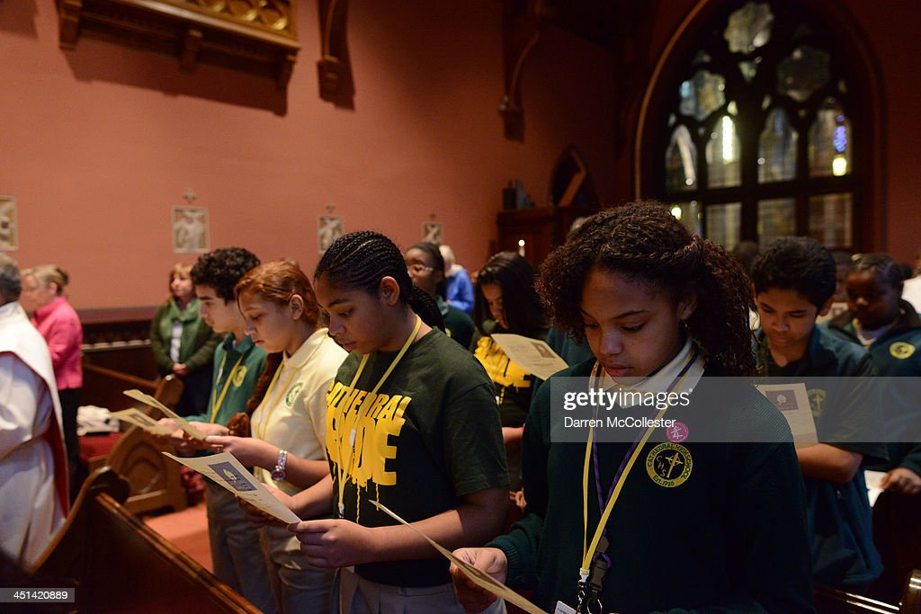Ayahna Simpson (R), a student at Cathedral High School, attends a mass to commemorate the 50th anniversary of the assassination of John F. Kennedy at the Blessed Sacrament Chapel in the Cathedral of the Holy Cross November 22, 2013 in Boston, Massachusetts. Kennedy, born in Brookline Massachusetts, was killed 50 years ago by Lee Harvey Oswald in Dallas Texas in 1963.
