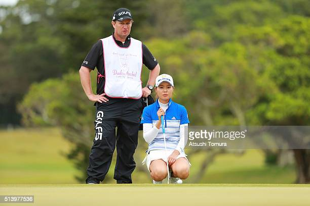Ayaka Matsumori of Japan lines up her birdie putt on the 14th green during the final round of the Daikin Orchid Ladies Golf Tournament at the Ryukyu...