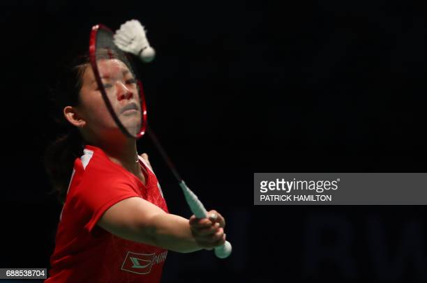 Ayaka Takahashi of Japan hits a return during the women's doubles Sudirman Cup match with partner Misaki Matsutomo against Vivian Hoo and Woon Khe...