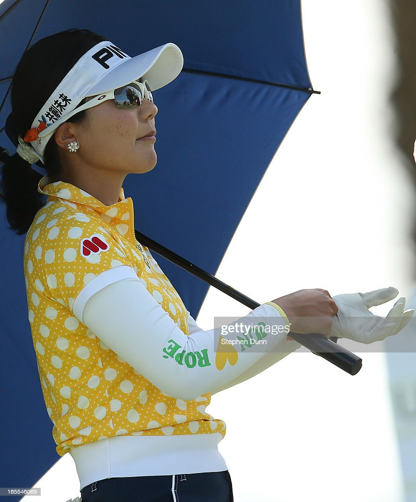 Ayako Uehara of Japan adjusts her glove before hitting her tee shot on the 16th hole during the first round of the Kraft Nabisco Championship at Mission Hills Country Club on April 4, 2013 in Rancho Mirage, California.