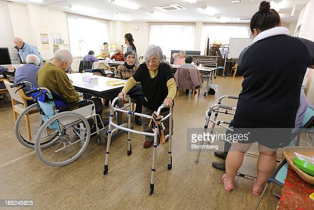 Ayako Wakasu center uses a walking frame as she walks through a day care facility on Gogo Island in Matsuyama Ehime Prefecture Japan on Friday March...