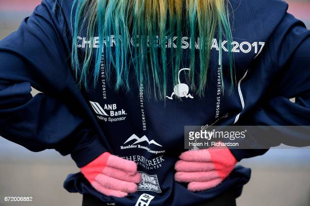 Ayala Flores of Castle Rock with brightly dyed hair and matching pink gloves and running tights waits at the finish line for friends during the 35th...