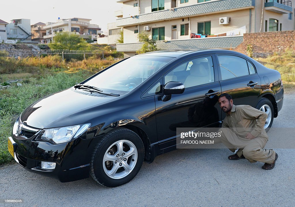 Ayaz, driver of journalist and television anchor Hamid Mir points out the place where a device in a metal box was hidden under the front passenger seat, in Islamabad on November 26, 2012. A high-profile Pakistani journalist and television anchor escaped an assassination bid on Monday when police defused a bomb planted under his car in Islamabad, police and his channel said. AFP PHOTO/Farooq NAEEM